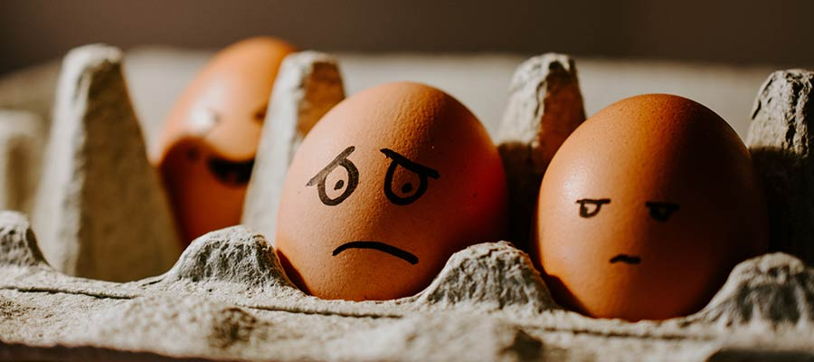 A carton of eggs with silly faces drawn on them.